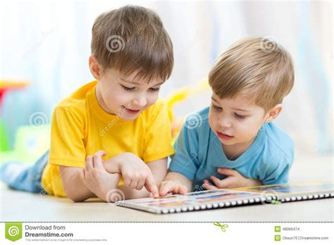 Two Children Looking At Book Stock Photo - Image of home